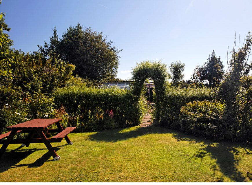 Keeping hedges shaped and clean is wonderful but allowing them to grow out and spread can be just as lovely. In this case, it gives this archway and hedged garden and care-free feel.