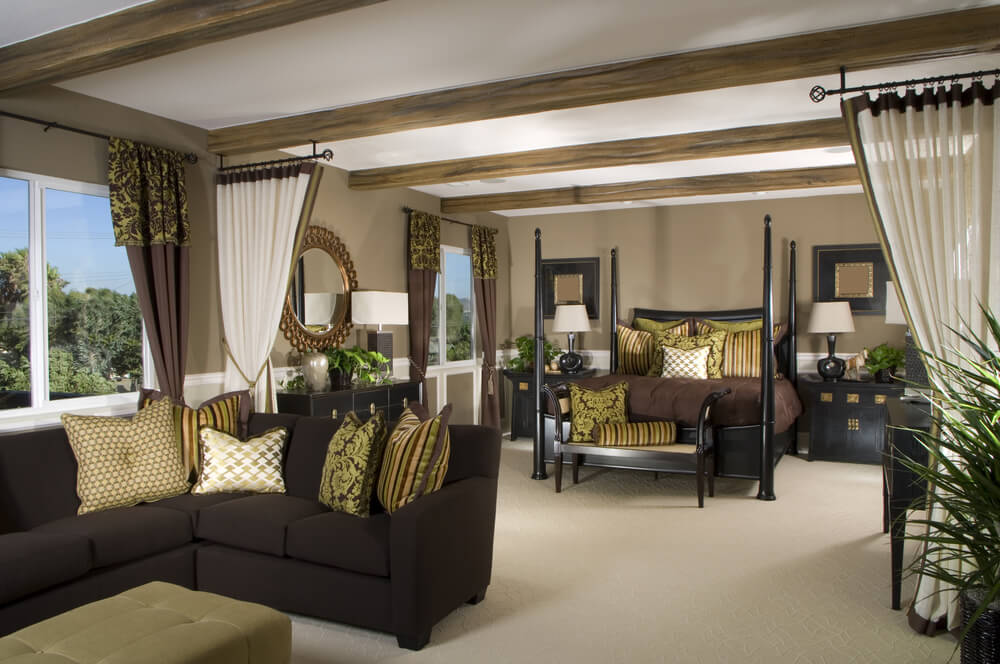 The chocolate brown sectional with patterned throw pillows ties the room together by matching the decorative pillows on the espresso four post bed and settee. Natural light is allowed to flood in when the dark drapery is pulled back, while the lighter, sage trimmed curtains as a room divider when pulled together. Dark modern lamps with light shades sit atop the black end tables with decorative gold drawer pulls. Several mirrored wall hangings on the beige walls add an additional feeling of spaciousness.
