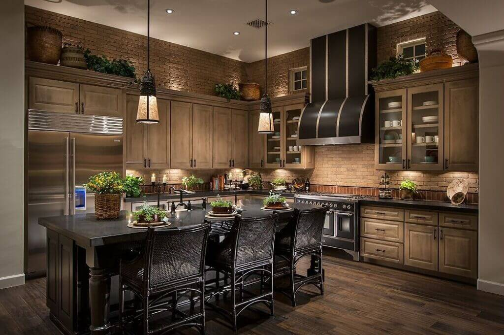 This beautiful kitchen has earth tone bricks lining the walls and a deep natural hardwood floor. The space is kept in a soft illumination in part to rustic hanging lights.