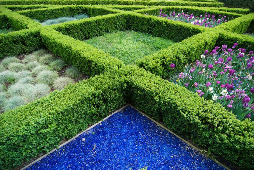 Using small hedges to create the lines of this gridded garden bed adds definition and structure to the natural shapes of the flowers.