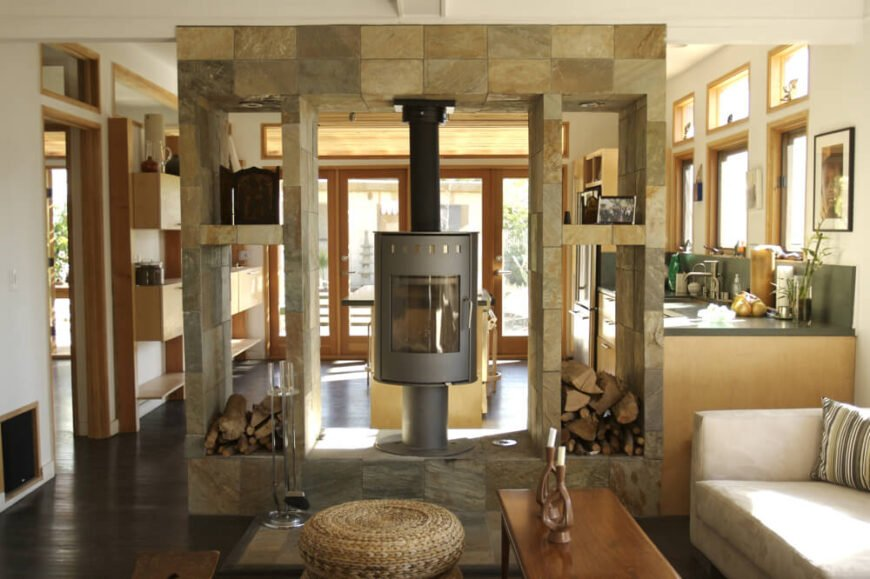 The impressive structure playing host to the furnace fireplace is made of gorgeous gray and brown patchwork stone tiles. A cream sofa sits quietly to the side, inviting guests to sit and enjoy the cozy warmth of the hearth.