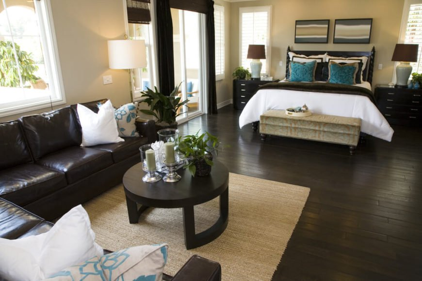 This bedroom features cream walls, ample natural light, and a stunning dark hardwood floor that coordinates with the furniture beautifully. A light textured area rug breaks up a look that might otherwise be too dark. Bold splashes of turquoise and bright white are made all the more apparent with the contrast of the dark sectional, coffee table, bed, and other furnishings.