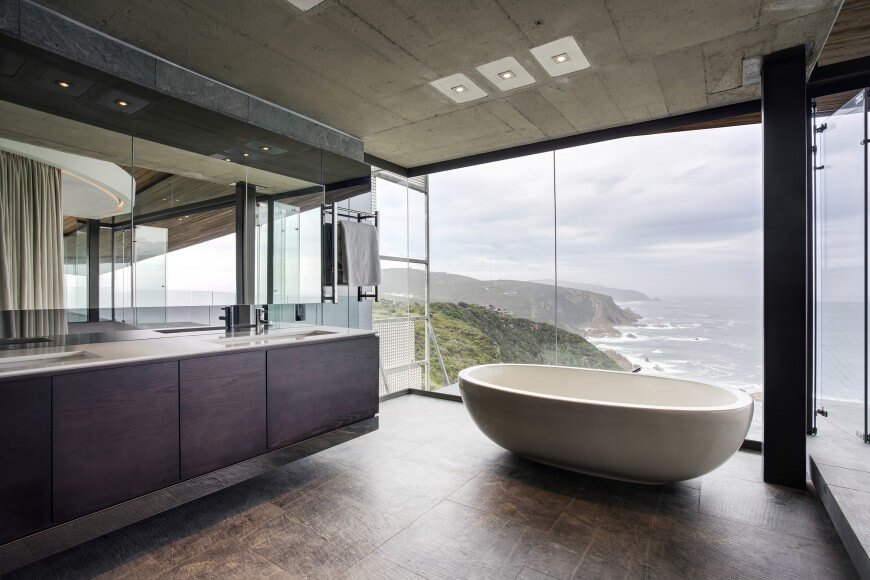 This amazing bathroom has a stunning view of the sea with external glazing. The dark natural hardwood in the vanity really brings the room together.