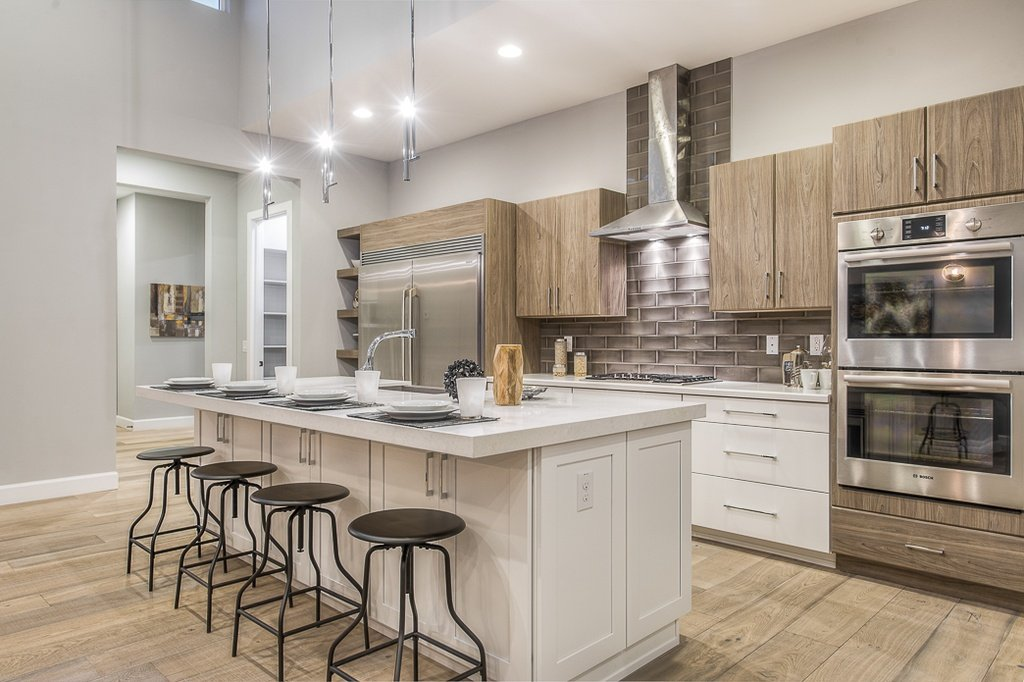 This kitchen has a classic atmosphere. A cloud white island stands tall in the center of the kitchen, draped in a soft white light from the metallic hanging lights.