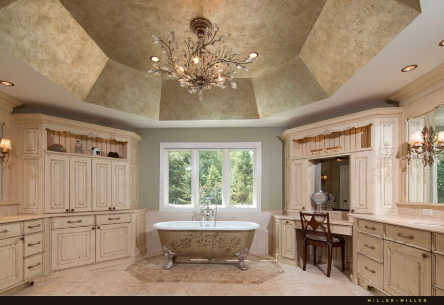 This classy bathroom features intricate designs on the bathtub and a large octogonal textured ceiling. A breath-taking chandelier with dainty crystal leaves lights this stunning space.