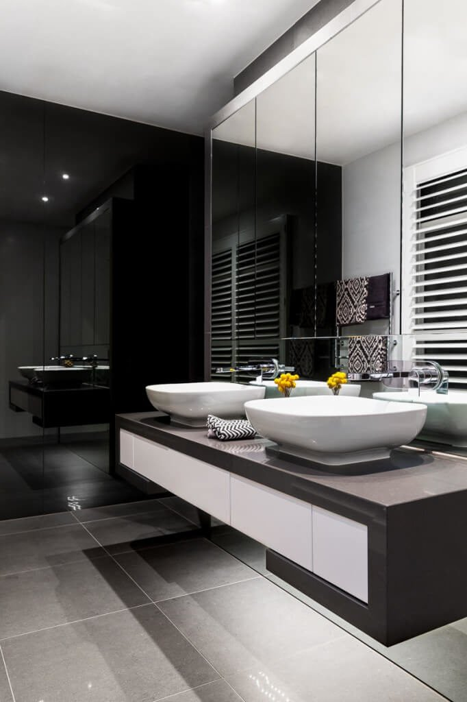 This chic design features a contemporary black and white color scheme. The square shaped vessel sinks really add to the modern look of this bathroom.