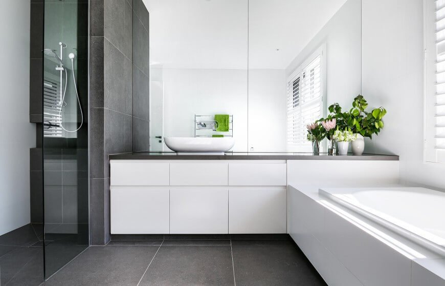 This bathroom has a very minimalist look with a modern color pallet. A large window offers a lot of light to illuminate the glossy white features in this space.