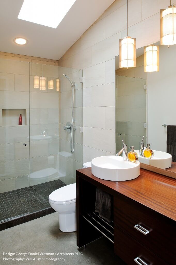 This dainty little bathroom has a contrast of black and natural hardwood in the vanity. A large glass enclosed shower stall has some black tiling for a sharp addition of color.