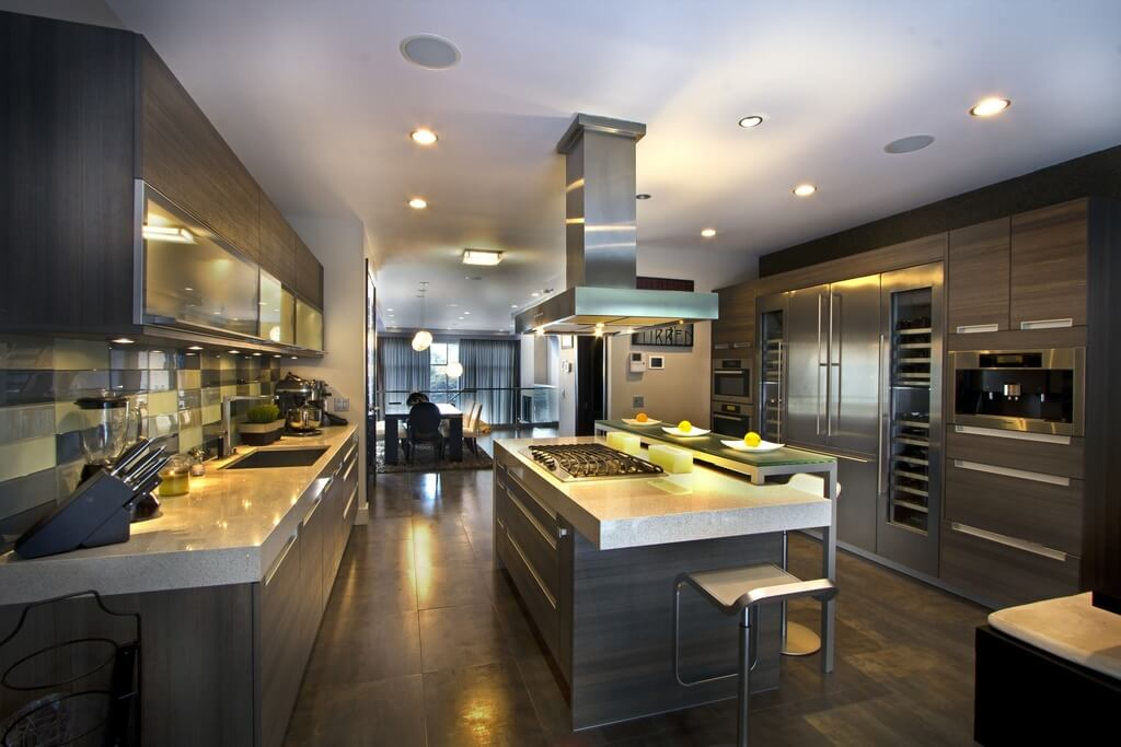 This space has a modern ambience. The countertops are lined with a chic granite that complements the grey of the cabinets. The kitchen is centralized in the home to give it an open floor plan.