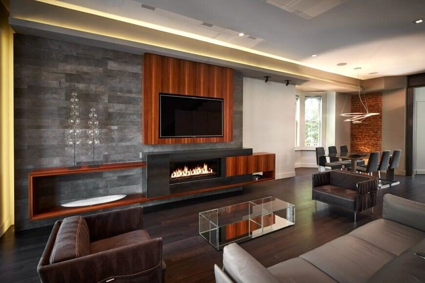 This highly modernized living room features sleek leather chairs and a sofa along with wooden accents and shelving with a heavy wood grain. The wall behind the entertainment center is in a beautiful dark stone tile, which acts as a contrast to the light neutrals on the other walls.