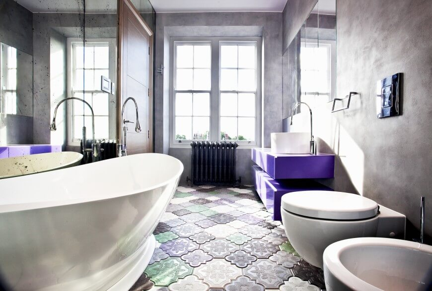 This whimsical bathroom favors the purple color pallet. This space also includes a cylinder shaped vessel sink and a large window for natural lighting.