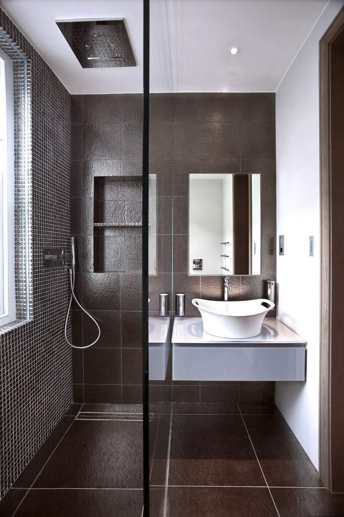 This elegant bathroom has a dark color scheme and a large glass enclosed shower. The vessel sink in this space is very unique and mimics a bucket.