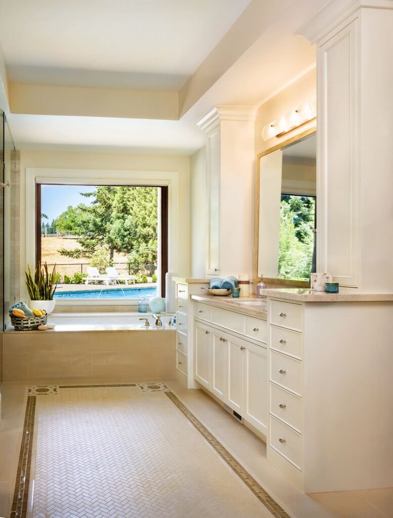 This bright room is filled with lots of natural light. The bathtub sits right beside a breezy window for a gorgeous and tranquil relaxation space.