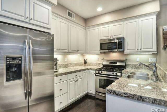 This quaint kitchen is illuminated by hidden lights under the cabinets and recessed fixtures. The beautiful granite countertops and brushed stainless steel glimmer under the bright lights.