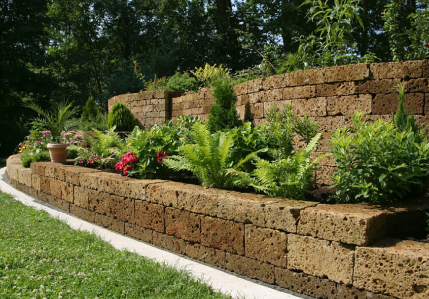 This stone wall has an interesting sponge texture to it. Bushes line the raised garden bed against the stone wall.
