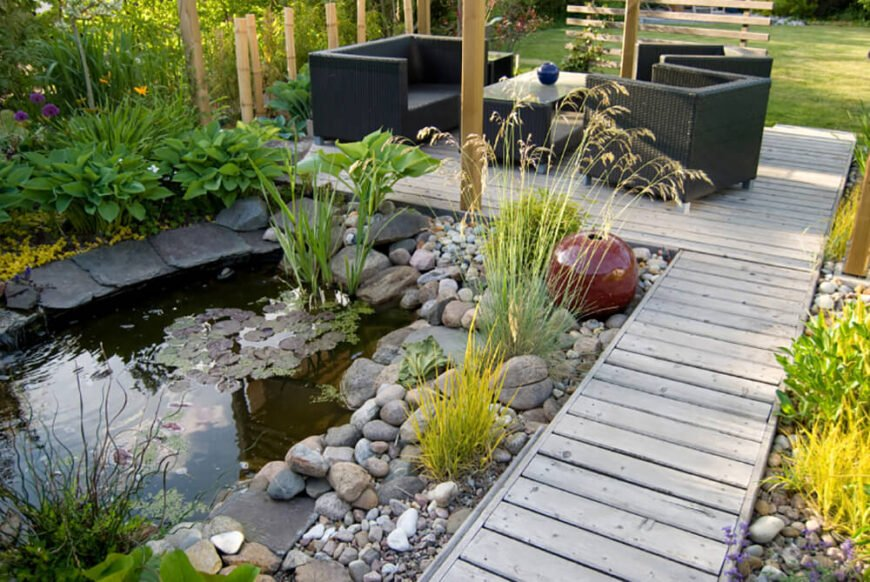 Here we can see the same garden from a different angle. A beautiful pond is surrounded by varying types of stones and grass.