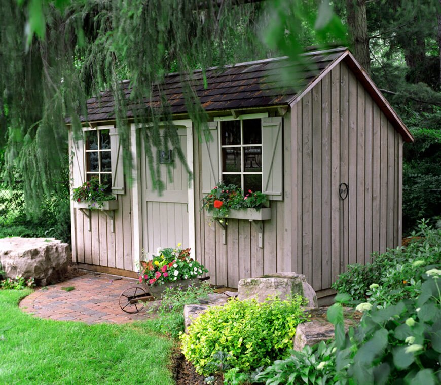 Here we can see a closeup of the rustic shed in the yard. Beautiful flowers grow under the windows of this quaint storage unit.
