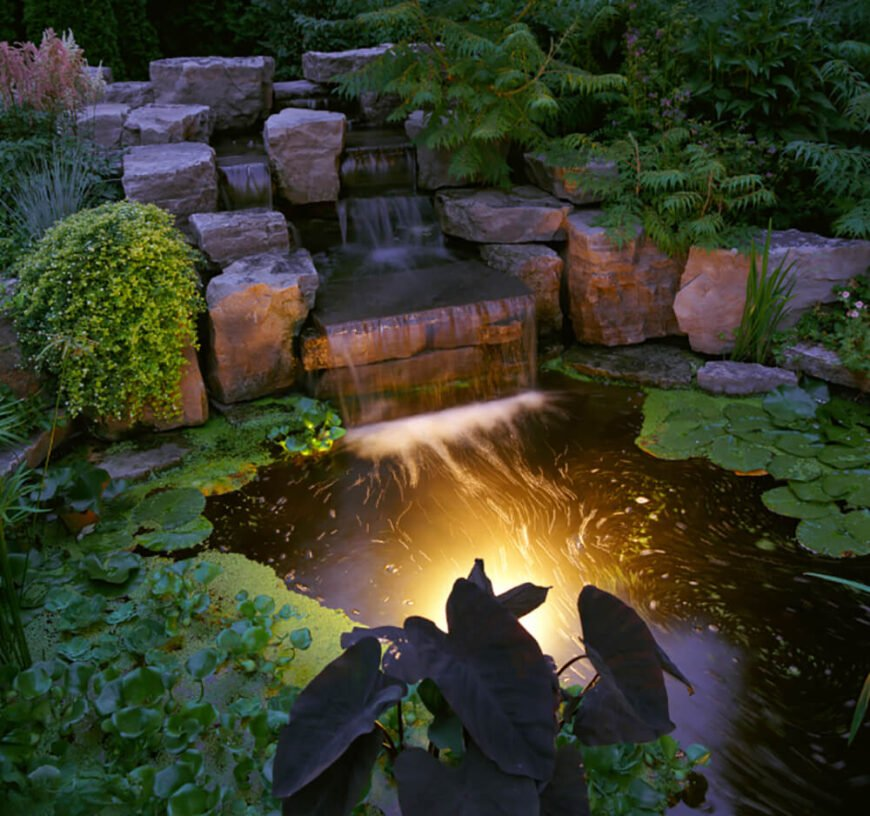Here we can see the gorgeous pond in the same garden. A soft glow lights up the water that flows from the stone waterfall.