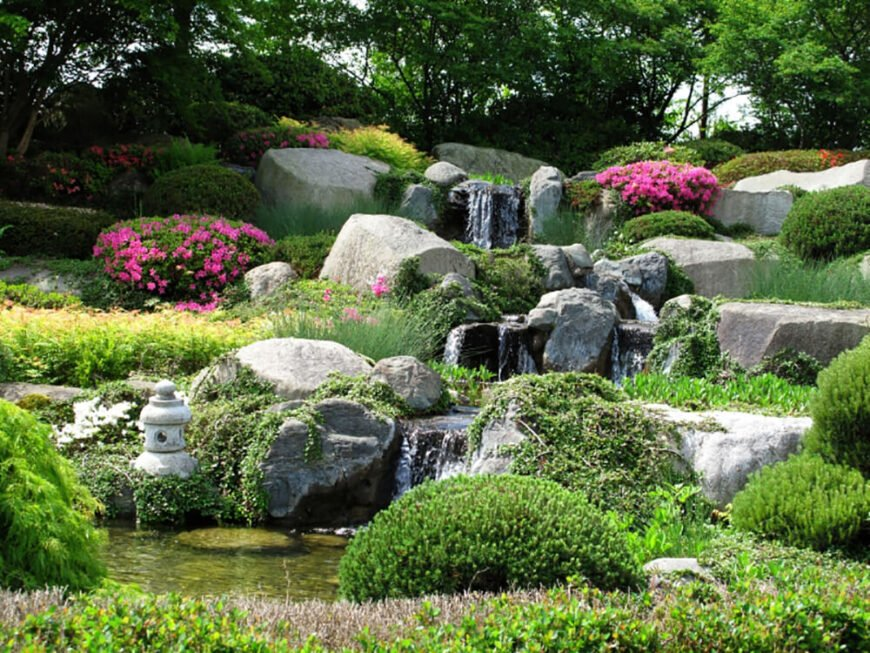 This waterfall is setup in the center of a garden full of different plants and flowers. The waterfall trickles down stones placed here and there before eventually pooling into a pond.