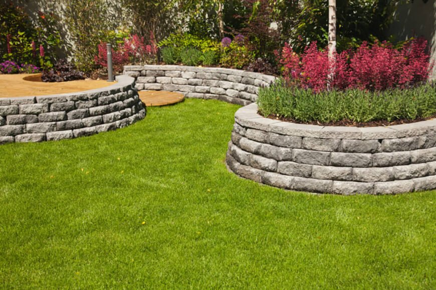 These raised stone flower beds break up the flat lawn and add interest to the yard. The deep pink flowers stand out well against the green surrounding them.