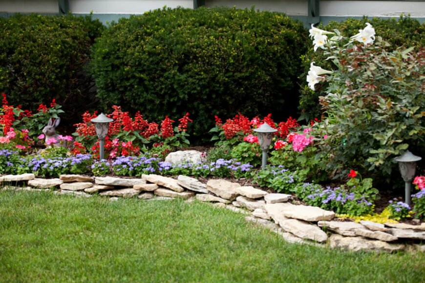 The use of garden sculptures and low whimsical lanterns give this flower bed a fantastic quality.