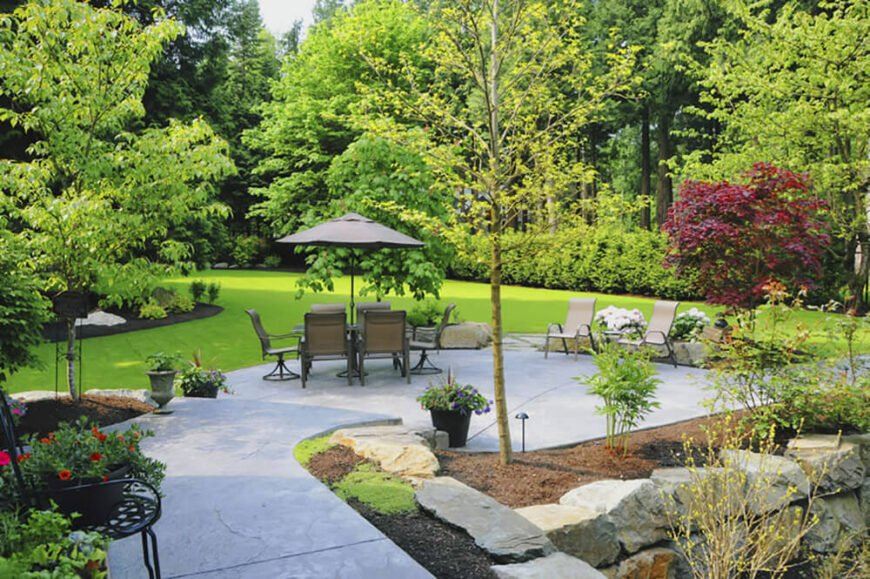 This lovely patio area looks out over a vast expanse of lush green lawn. Balancing the lightness of the patio and the grass with dark mulch in the flower beds makes the little islands stand out in the sea of green.