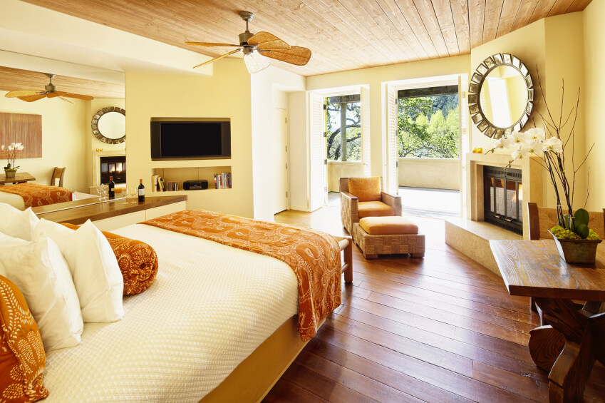 Oranges and yellow tones take center stage in this stunning bedroom. Wide plank wood flooring complements the look nicely. A large mirror can be seen beside the sleeping area, reflecting the other side of the room and adding the illusion of more space. An inset wall mounted television is in full view of the bed.