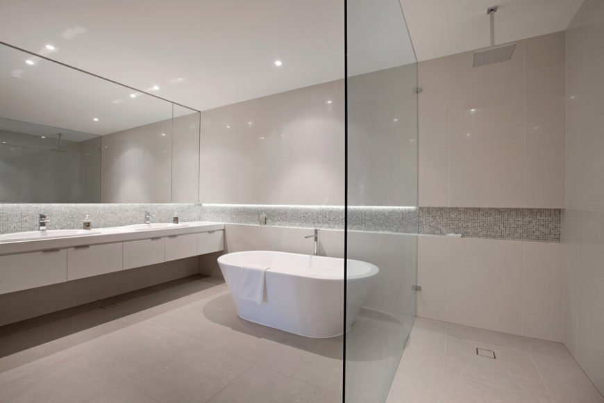 The primary bathroom is an expansive, open space with a large walk-in shower divided by glass, and a white soaking tub at center. The dual vanity runs the length of the room with sleek white cabinetry.