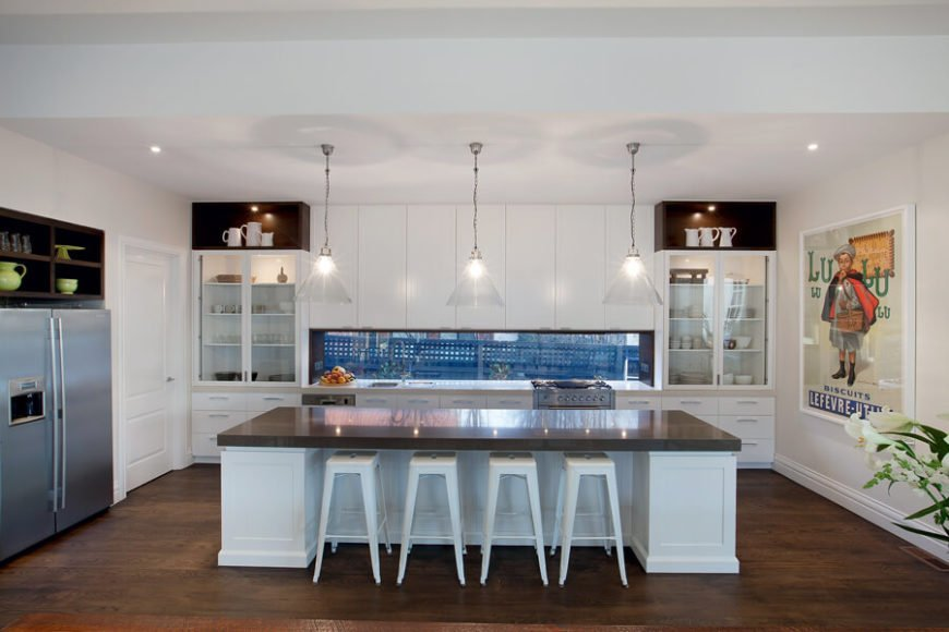 The kitchen stands in a minimal-fuss open-plan design, centered on a massive island with thick dark countertop over white construction. Over the island, we see the glass backsplash, allowing for outdoor views in a surprising place.