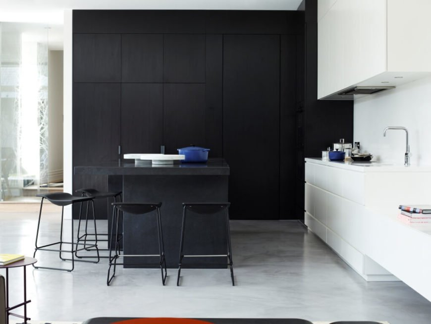 From here we see the high contrast defining this corner of the open-plan space. Sleek white cabinetry surrounds the sink and matching countertops, while an imposing set of floor to ceiling dark wood cabinets fills the remaining wall space.