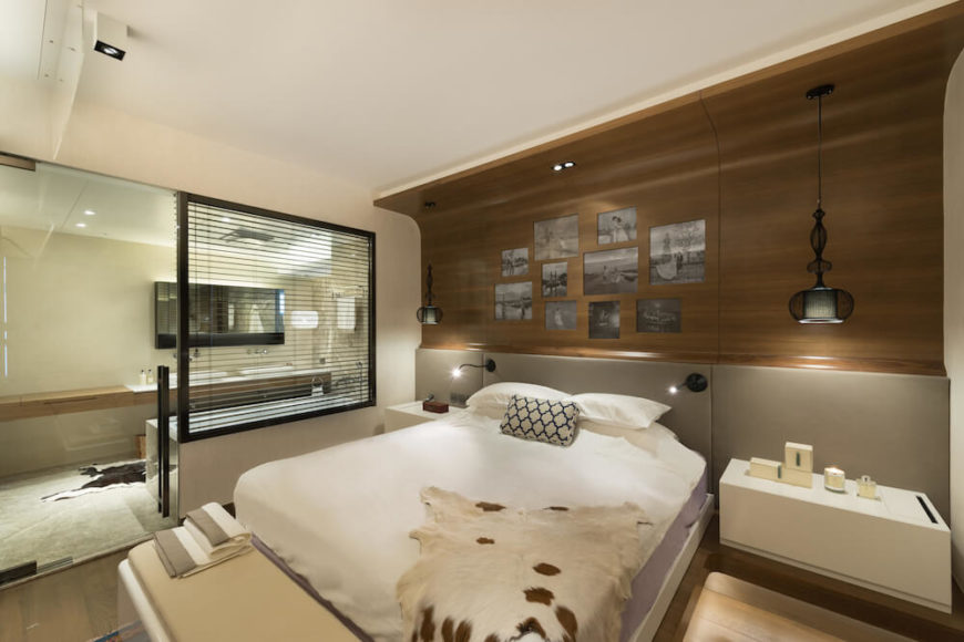 This natural looking bedroom has a large wooden and curved headboard that holds personalized photos. A glass wall separates the bathroom from the bedroom.