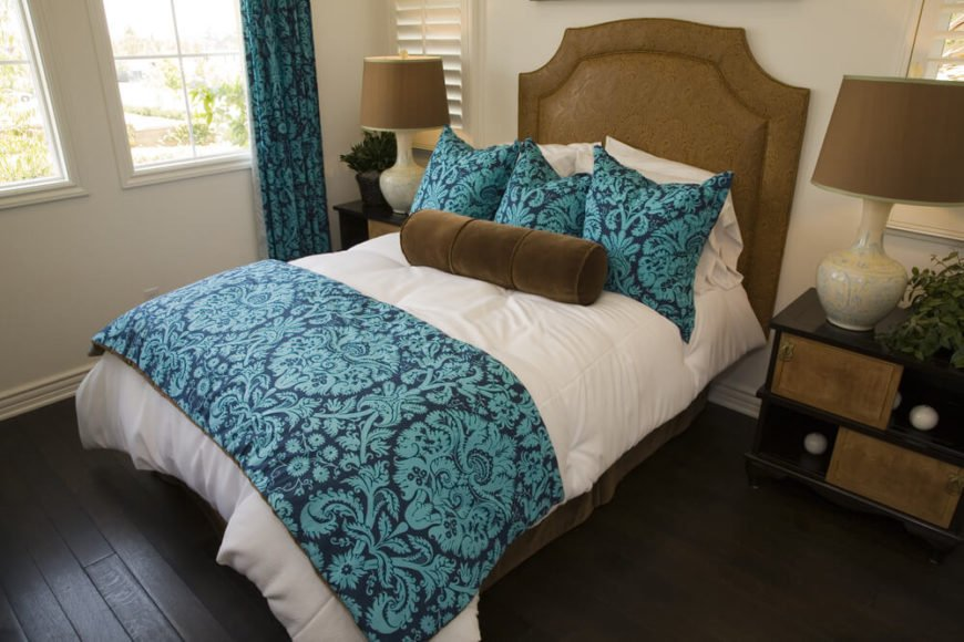 A colorful bed and dark hardwood flooring contrast beautifully in this bedroom. The fabric headboard has a very fine pattern and is complemented by the bold pattern of the bed linens.
