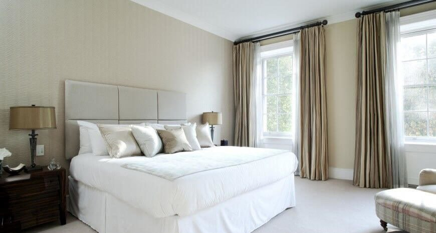 This bedroom has a very elegant and gentle appearance to it. The headboard in this space has a unique square pattern that is different from the classic button-tufted look.
