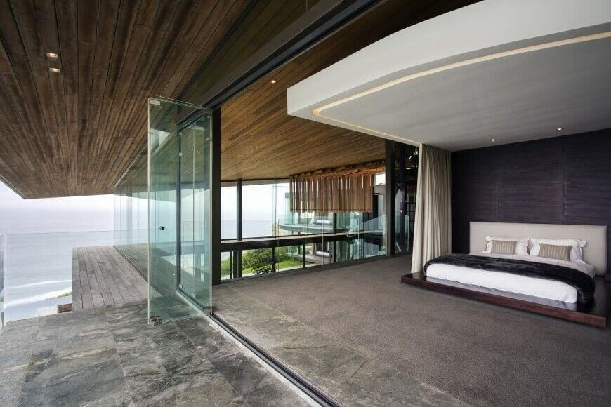This home is absolutely breath-taking, with a bedroom encased by glass with a view of the open sea. The fabric headboard in this room contrasts the deep natural wood on the walls of the bed space.