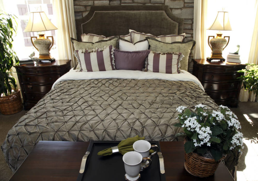 This luxurious bed has hints of plumb and white against the rich chocolate color of the headboard. This design is very elegant and chic with stunning decor and plants around the room.