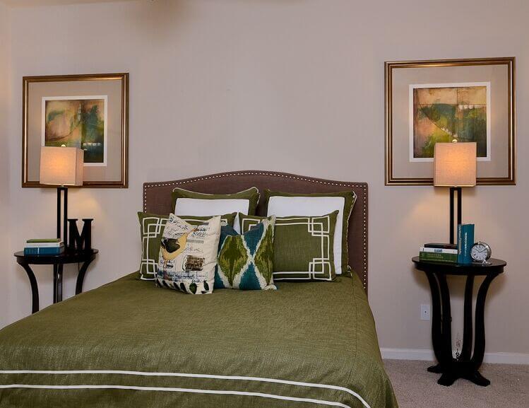 This bed has very powerful earthy tones. The deep brown fabric headboard and the green pillows and sheets create a really natural color scheme.