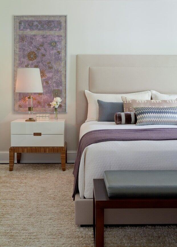 The headboard on this king size bed is very subtle, and matches the coloring of the walls. Your attention here is directed to the various blues and purples on the sheets of the bed.