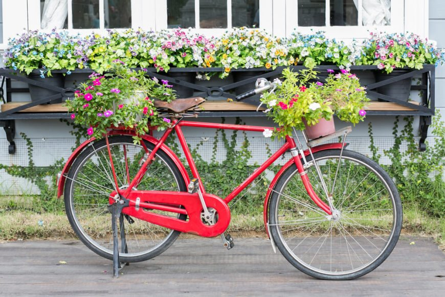 The use of an antique bike adds a bit of rustic charm to the front of this house. The large window box planter is a nice, sturdy touch.