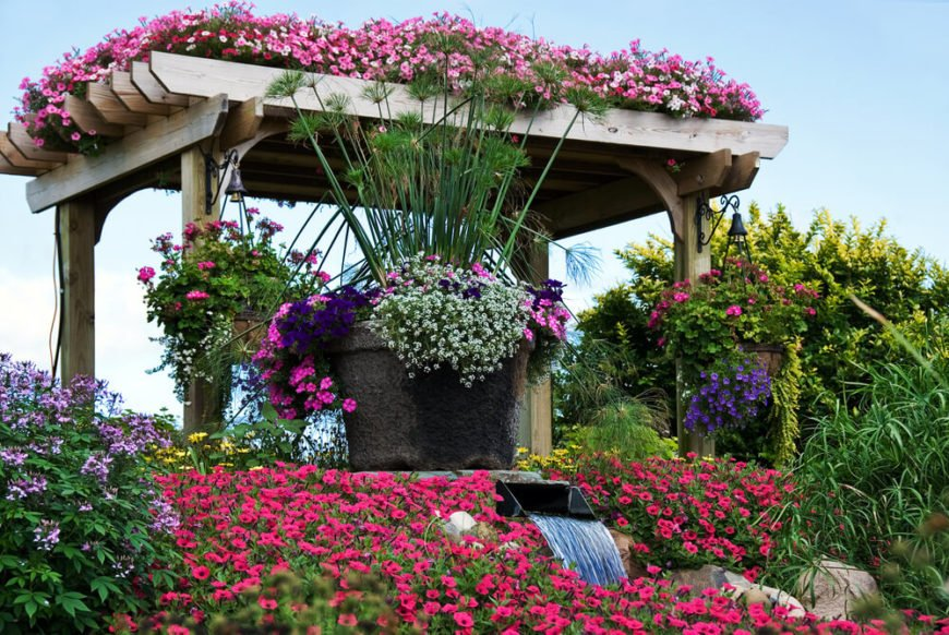 This arbor, complete with water feature, is a glorious touch to this garden. Planting on the roof and utilizing the sides to hang baskets of flowers turns the whole thing into a planter.