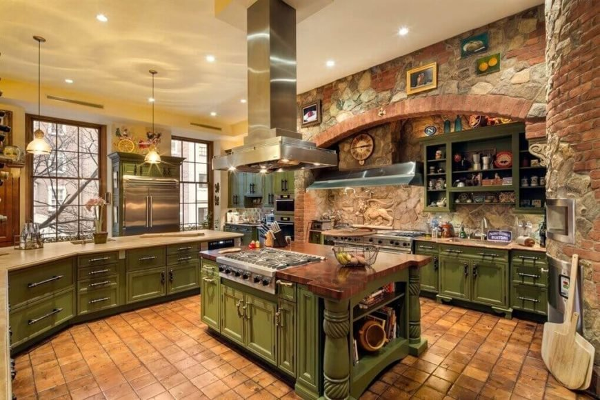 In this massive rustic kitchen, green painted wood cabinetry and stone walls compete with brown tile flooring in an abundance of textural detail. The large island at center features thick polished wood countertop and built-in stainless steel stove.