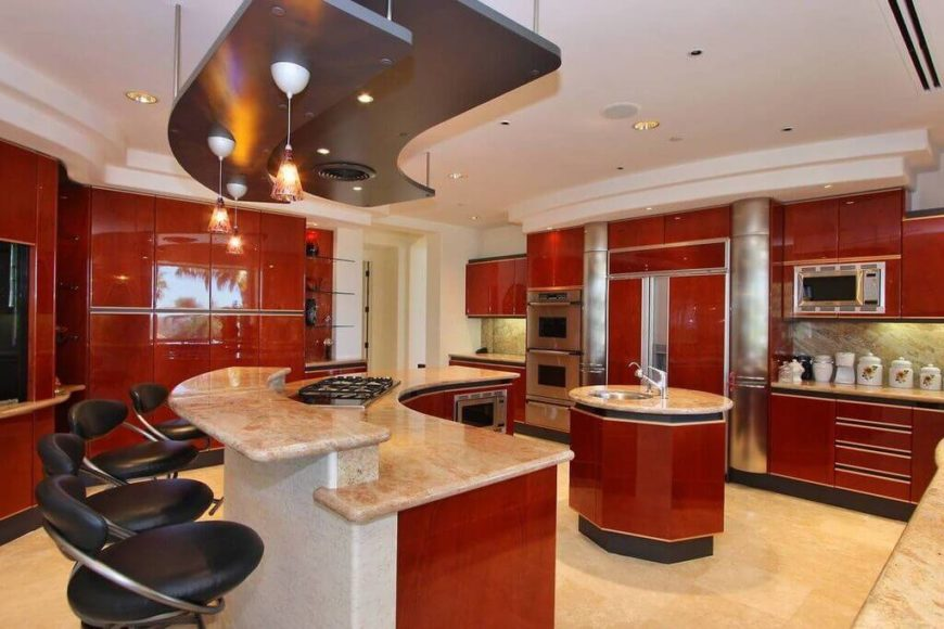 This modern kitchen is highlighted with bold red wood cabinetry throughout, contrasting with beige tile flooring and granite countertops. A smaller circular island boasts a sink, while the larger C-shaped island features a built-in range and upper tier for dining.