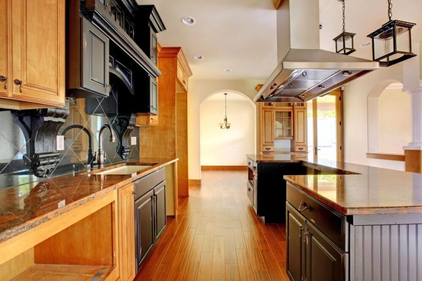 This lengthy kitchen is flush with warm natural wood tones, from the flooring on up. The immense U-shaped island at right features a cavity for the placement of a full size stove and range, right below the large stainless steel hood vent.