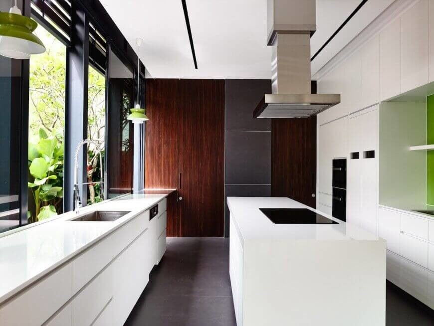 In another minimalist and modern kitchen, we see a rich array of textures, including sleek white cabinetry and countertops, charcoal tile flooring, and rich wood detail on the far wall. The white island features a sleek black cooktop beneath a stainless steel hood vent.