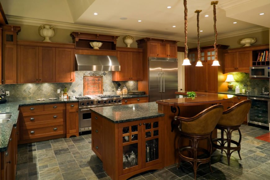 In this dark hued, utterly bespoke kitchen, sharp contrast is achieved via juxtaposing between dark floor tiling and matching-toned granite countertops against rich wood cabinetry. The island features glass door cabinetry and a two-tier design, with an upper level in rich wood for dining purposes.