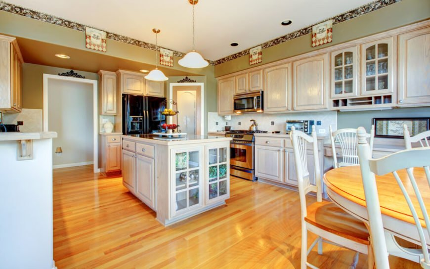 The bright and bold nature of this kitchen is highlighted by warm hardwood flooring and rustic white painted cabinetry. The wide space centers on a beautiful island with glass panel cabinetry and sleek, dark toned countertop space.