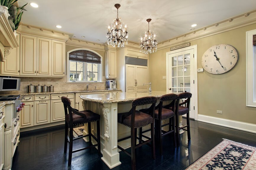 In a luxuriously detailed kitchen, high contrast informs the overall style. Dark hardwood flooring matches light beige cabinetry, while the granite topped island features ornate carved detail and abundant room for in-kitchen dining, courtesy of a set of leather upholstered bar stools.