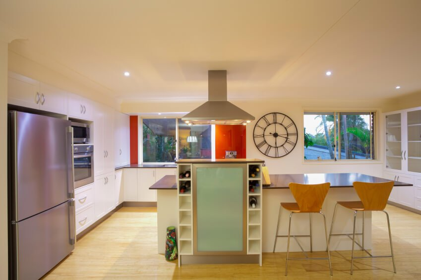 This ultra-modern kitchen shrugs off the usual buttoned-down look of its contemporaries with flashes of bright color throughout. The island features an expansive dark countertop with dining space, plus a tall wine rack and cooled storage rising above. This extra feature backs up a built-in range, with stainless steel hood vent overhead.