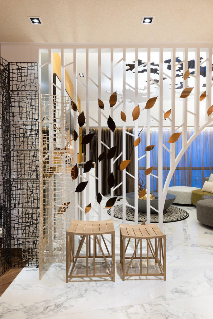 """The entrance into the apartment faces the living room and is met with warm toned autumn leaves """"blowing"""" up to the ceiling on an unseen wind."""