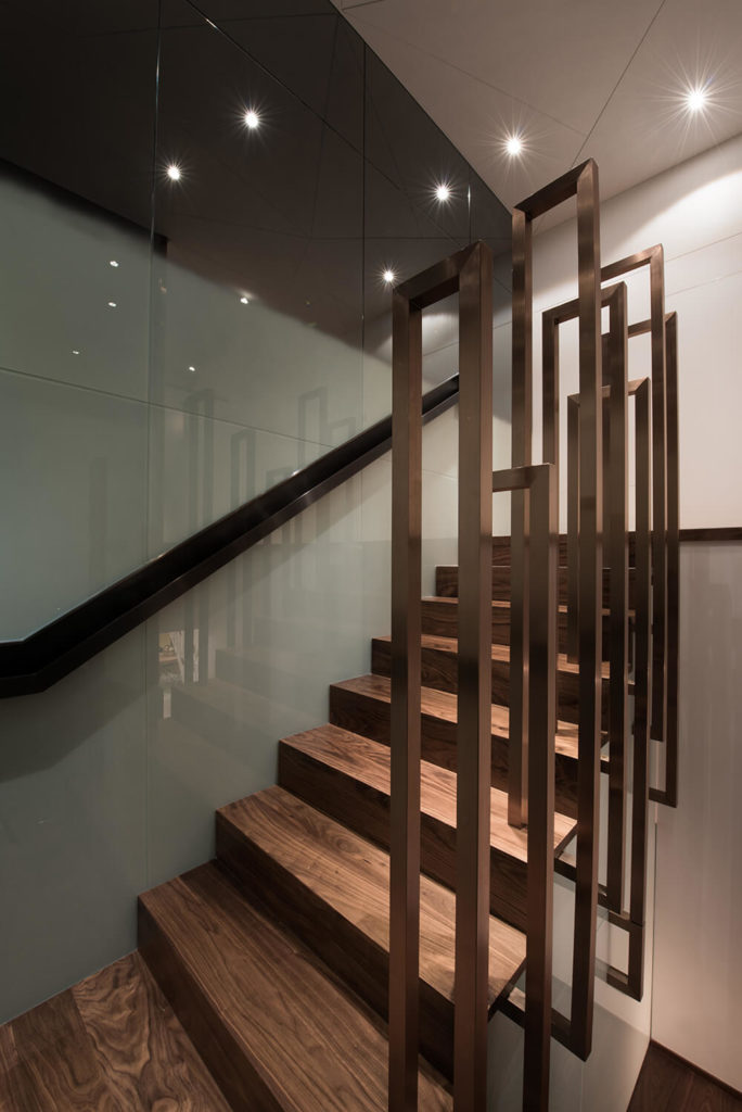 The stairs up the second floor are finished in a beautiful rose gold color. The handrail mimics the elongated shape of tree stems and leads the eye up to the second floor.
