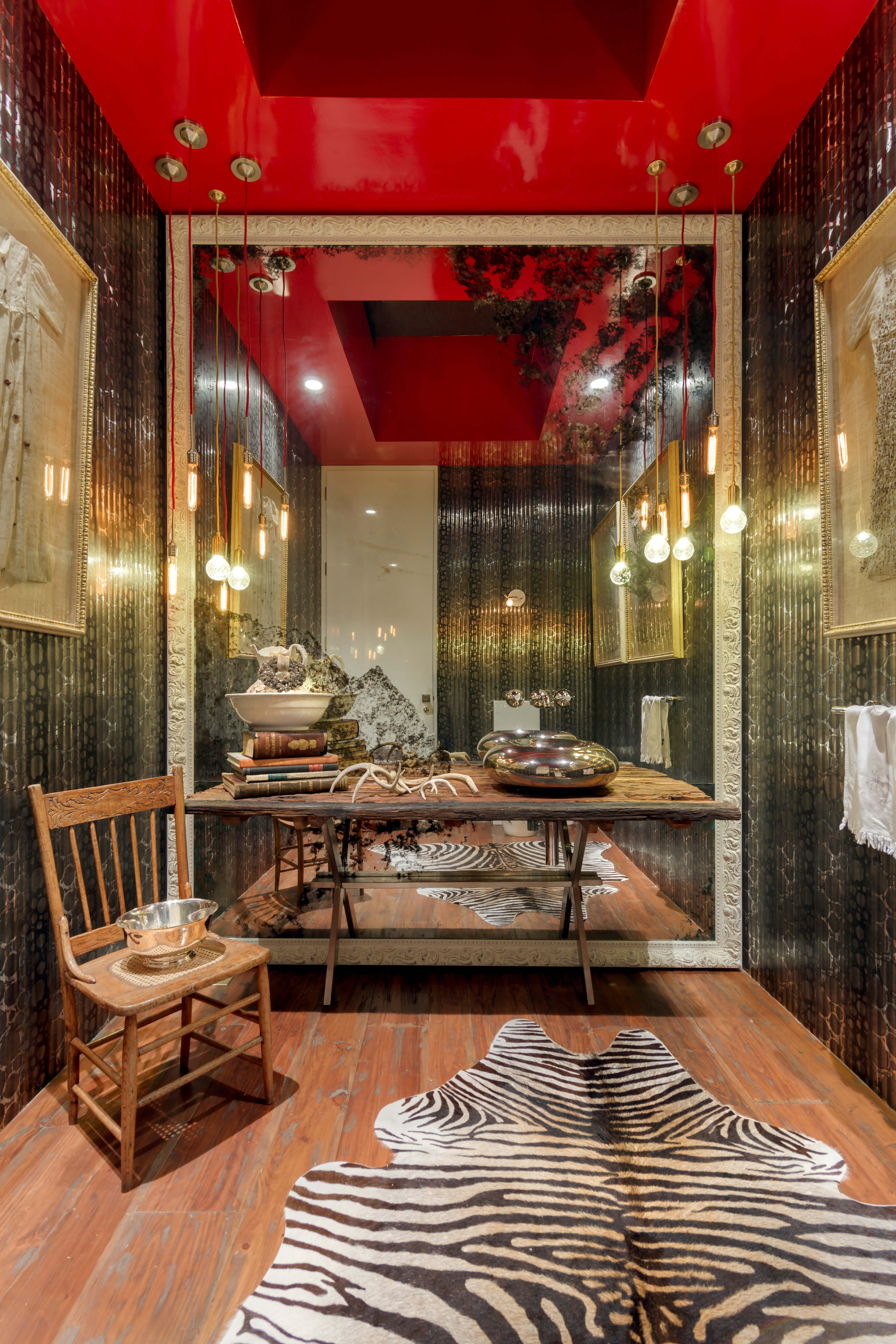 The ultra-evocative bathroom sports hardwood flooring and a rustic vanity, contrasting with reflective walls and a room-size mirror. An innovative vessel sink sparkles in chrome, with mirror-mounted plumbing above.